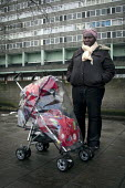 A resident with her child in a pushchair, Aylesbury Estate, Walworth, London. - Connor Matheson - ,2010s,2012,adult,adults,BAME,BAMEs,BENIFIT,BENIFITS,Black,blocks,BME,bmes,child,CHILDHOOD,children,cities,city,claimant,claimants,council estate,council services,council estate,council services,depri