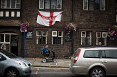 A man on a mobility scooter rides past an england flag outsiide a pub. Rotherham Centre, South Yorkshire. - Connor Matheson - 2010s,2014,communities,community,disabilities,disability,disable,disabled,disablement,EBF,Economic,Economy,flag,flags,incapacity,LICENSED,Low Income,male,man,men,minorities,mobility,mobility scooter,m