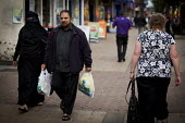 A muslim couple walk past a white woman. Rotherham Centre, South Yorkshire. - Connor Matheson - 28-08-2014