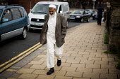 A muslim man walks down the street. Rotherham Centre, South Yorkshire. - Connor Matheson - 2010s,2014,BAME,BAMEs,Black,BME,bmes,communities,community,diversity,ethnic,ethnicity,ISLAM,ISLAMIC,Low Income,male,man,men,minorities,minority,monotheistic,MUSLEM,muslim,muslims,pedestrian,pedestrian