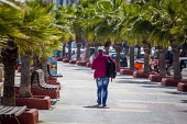 A tourist walking along a street lined with palm trees. sliema, Malta. - Connor Matheson - 23-04-2015