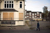 A view of housing. Woman walking past a closed pub. Scunthorpe, North Lincolnshire. - Connor Matheson - ,2010s,2014,Boarded Up,closed,closing,closure,closures,derelict,DERELICTION,disused,EBF,Economic,Economy,EQUALITY,excluded,exclusion,FEMALE,HARDSHIP,house,houses,Housing Estate,impoverished,impoverish