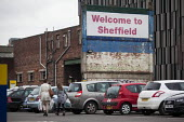 A woman and her daughter walking through a car park with a welcome to Sheffield sign. Sheffield, South Yorkshire. - Connor Matheson - 14-03-2015