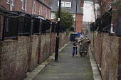 An asian woman with a child walking down the back ally of a row of terrace houses. Highfield, Sheffield, South Yorkshire. - Connor Matheson - 2010s,2015,adult,adults,age,ageing population,asian,asians,BAME,BAMEs,Black,BME,bmes,boy,boys,building,buildings,child,CHILDHOOD,children,cities,city,diversity,elderly,EQUALITY,ethnic,ethnicity,exclud