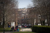 Parents walking across a park. London Road, Sheffield, South Yorkshire. - Connor Matheson - 2010s,2015,building,buildings,cities,city,families,FAMILY,highway,house,houses,housing,Leisure,LFL,LIFE,London,outdoors,PARENT,parenthood,PARENTING,Parents,Park,parks,PEOPLE,RECREATION,RECREATIONAL,Ro