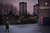 A student walking home past tower blocks. Eccesall Road, Sheffield, South Yorkshire. - Connor Matheson - &,2010s,2015,alone,at,attention,attentive,blocks,building,buildings,cities,city,dusk,evening,headphones,High Rise,highway,home,housing,intelligence,intelligent,interested,isolated,isolation,leisure,lf