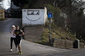 Runners running past a garage with a smiling face and a comical slogan written in the Yorkshire dialect, Ecclesall, Sheffield, South Yorkshire. - Connor Matheson - ,2010s,2015,cities,city,communicating,communication,EMOTION,EMOTIONAL,EMOTIONS,english,FEMALE,funny,garage,height,high up,hill,hills,hobbies,hobby,hobbyist,humor,humorous,HUMOUR,jogger,joggers,jogging