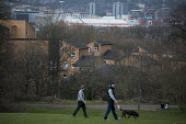 Two men walking their dogs in a park a view of housing and the Sheffield United football grounds. Sheffield, South Yorkshire. - Connor Matheson - 2010s,2015,animal,animals,canine,cities,city,cityscape,cityscapes,Council Services,Council Services,dog,dogs,football,Leisure,LFL,LIFE,local authority,male,man,men,outdoors,outside,OWNERSHIP,Park,park