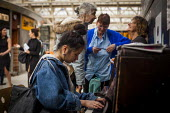 A young woman playing the piano in Sheffield Railway Station. The piano is inspired by the street piano scheme, aimed at bringing access to instruments to a wider audience. Sheffield Centre, South Yor... - Connor Matheson - 08-04-2015