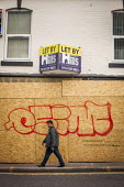 A local man walks past a retail unit to let with Graffiti on the front. London Road, Sheffield, South Yorkshire. - Connor Matheson - 15-04-2015