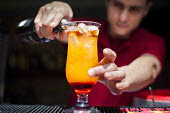 A hotel worker making a tequilla sunrise cocktail. Tourism is a vital industry for the maltese economy, contributing 15 to its GDP. Since 2009 Malta has experienced a 10 drop in tourism. Tropicana Hot... - Connor Matheson - 21-04-2015