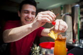 A hotel worker making a tequilla sunrise cocktail. Tourism is a vital industry for the maltese economy, contributing 15 to its GDP. Since 2009 Malta has experienced a 10 drop in tourism. Tropicana Hot... - Connor Matheson - 1st,2010s,2015,alcohol,Bar staff,capitalism,capitalist,caterer,caterers,catering,dawn,dawning,day,daybreak,drink,drinking,drinks,EARNINGS,EBF,Economic,Economy,employee,employees,Employment,EQUALITY,eu