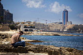 A local workman relaxes by the sea while listening to his Ipod with the Hilton Hotel and Sain julians in the background. Sliema, Malta. - Connor Matheson - 2010s,2015,attention,attentive,break,break time,breaktime,coast,coastal,coasts,employee,employees,Employment,eu,european,europeans,eurozone,intelligence,intelligent,interested,Ipod,job,jobs,lbr,listen