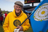 A volunteer for the Tour De Yorkshire with a Yorkshire flag. Roundhay Park, Leeds, West Yorkshire - Connor Matheson - 2010s,2015,bicycle,bicycles,BICYCLING,Bicyclist,Bicyclists,BIKE,BIKES,cities,city,cycle,cycles,cycling,Cyclist,Cyclists,Leeds,PHYSICAL,race,races,racing,spo,sport,sports,urban,volunteer,VOLUNTEERS,Yor