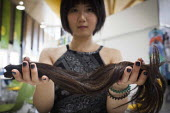 A Chinese student who has cut her own hair in order to sell it to Bloomsbury Wigs in London. She hopes to get around �50 for her hair which was 19 inches long. Some people with rare hair types have ma... - Connor Matheson - 2010s,2015,Asian,Asians,BAME,BAMEs,BME,bmes,body parts,chinese,cities,city,communicating,communication,cut,cutting,Diaspora,diversity,EQUALITY,ethnic,ethnicity,excluded,exclusion,FEMALE,foreign,Foreig