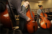 Pupils learn the double bass with a musician from the Royal Liverpool Philharmonic Orchestra. Pupil in a music lesson at Sacred Heart Catholic Primary School and Kensington Junior & Infant School in L... - Christopher Thomond - ,2000s,2008,ACE,ace culture arts,arts,BAME,BAMEs,black,BME,BME Black minority ethnic,bmes,boy,boys,Catholic,child,CHILDHOOD,children,class,classroom,classrooms,cultural,culture,diversity,double bass,e