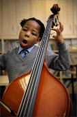 Pupil in a music lesson at Sacred Heart Catholic Primary School and Kensington Junior & Infant School in Liverpool. - Christopher Thomond - 2000s,2008,ACE,ace art culture arts,arts,BAME,BAMEs,Black,BME,BME Black minority ethnic,bmes,Catholic,child,CHILDHOOD,children,class,classroom,classrooms,culture,diversity,double bass,edu,edu educatio