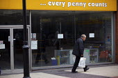 An elderly shopper walking through Rotherham town centre walks past a closed shop Every Penny Counts... - Christopher Thomond - 23-07-2009