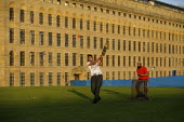 Young men play an impromptu cricket match outside Lister's Mill in Bradford, once the largest silk factory in the world, now partly renovated turned into an apartment block. - Christopher Thomond - 2000s,2009,and,apartment,areas,asian,asians,ball,balls,BAME,BAMEs,bat,bats,Black,block,blocks,BME,BME minority ethnic,bmes,building,buildings,cities,city,CLOSED,closing,closure,closures,Cricket Match,