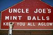 Painting the sign at The Uncle Joes Mintballs Works in Wigan - Keep you all aglow. - Christopher Thomond - 15-09-2009