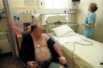 Nurse checking the blood pressure of a Cardiac Patient at a North London Hospital - Duncan Phillips - 2000,2000s,blood,Cardiac,Care,checking,cities,city,condition,diet,diets,fat,female,hea,HEA health,Health,HEALTH SERVICES,healthcare,heart,Hospital,HOSPITALS,job,jobs,LAB LBR work,London,male,medicine,