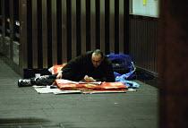 Homeless on the street London Victoria - Duncan Phillips - ,2000s,2002,a,asleep,cities,city,Eating,EXHAUSTION,food,FOODS,homeless,homelessness,London,newspaper,NEWSPAPERS,press,RAIL,railway,RAILWAYS,READ,reading,READS,rough,Rough Sleeper,Rough Sleepers,sandwi