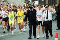 Injured runner being helped by St John Ambulance Brigade Volunteers Flora London Marathon - Duncan Phillips - 2000s,2002,Ambulance,AMBULANCES,ankle,cities,city,enjoying,enjoyment,EXERCISE,exercises,exercising,fitness,fun,health,Injured,INJURIES,injury,LFL leisure,london,Marathon,people,PHYSICAL,Physical Fitne