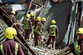 Firefighters hand searching a collapsed building where there was the possibility of trapped building workers. North London - Duncan Phillips - 16-06-2002