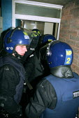 Police Officer in Riot Gear entering a property where hard drugs are suspected of being sold. - Duncan Phillips - 27-05-2002
