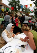 Women having a manicure in aid of the local hospice at a street party in Sheffield - David Bocking - 2000s,2001,ACE culture,asian,at,BAME,BAMEs,Black,BME,bmes,bunting,CHILD,CHILDHOOD,children,communities,community,diversity,dress,ethnic,ethnicity,FEMALE,hajib,headscarf,hijab,hospice,islam,islamic,juv