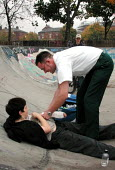 South Yorkshire Ambulance Service paramedic helping a boy who'd just broken his wrist in a skateboard accident - David Bocking - 2000s,2001,accident,Accident and Emergency,accidental,ACCIDENTS,adult,adults,ambulance,AMBULANCES,boy,BOYS,broken,care,child,CHILDHOOD,children,driver,DRIVERS,DRIVING,EXTREME,game,games,HEA,health,HEA