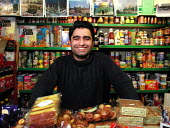 32 year old Corner Shop owner in front of some of his stock (and pictures of famous Mosques), Sheffield - David Bocking - 08-01-2002