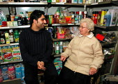 32 year old corner shop owner talking to a customer at the back of his store in Sheffield - David Bocking - 08-01-2002