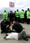 Barbara Maver & Sue Brackenbury (fore) from Faslane Peace Camp with a lock on tube on their arms prior to being arrested at the CND anti Star Wars demonstration at Fylingdales RAF base on 15th June 20... - David Bocking - 15-06-2002