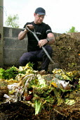 City farm worker turning compost made from organic vegetable waste - David Bocking - 03-05-2005