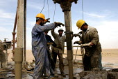 Workers on an oil drilling rig in the South Rumeila oil field outside of Basra, in southern Iraq. Workers in Iraqs oil industry have organized one of the countrys strongest unions, and are trying to p... - David Bacon - , Iraqis,2000s,2005,Arab,Arabs,Basra,capitalism,capitalist,drill,drilling,EBF Economy,engineer,engineers,field,fields,Industries,industry,Iraq,Iraqi,Iraqis,job,jobs,LAB LBR Work,maker,makers,making,ma