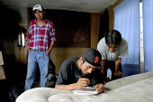 Migrant workers calculating their share of the rent for a house trailer where they live with seven others in a small mobile home park. They and about 60 other migrants live on the outskirts of Salinas... - David Bacon - 2000s,2006,accommodation,AGRICULTURAL,agriculture,America,americans,Amerindian,Amerindians,bme minority ethnic American,calculating,California,capitalism,capitalist,crowding,Diaspora,EARNINGS,employee