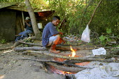 Juan, a Chinanteco migrant farm worker from Oaxaca, makes a fire in front of the shack where he lives with other migrants under the trees in Sonoma County. California USA - David Bacon - 05-08-2006