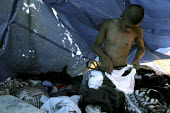 A young man gets dressed in his sleeping tent in a camp set up by migrant workers from the Mexican state of Oaxaca, who live in temporary shelters next to a field of wine grapes. The workers are Chati... - David Bacon - 26-06-2004