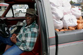 A South Carolina farmer sells sweet potatoes from the back of his pickup truck in the parking lot where workers at the Smithfield pork plant in Tarheel, North Carolina, wait for vans to take them to t... - David Bacon - 13-03-2006