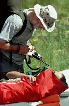 Peak District national park ranger taking details from an injured hang glider pilot after a mountain rescue on Mam Tor - David Bocking - 10-08-1998