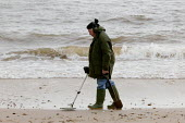 Retired elderly man, well wrapped up against the winter cold, is seen using his metal detector on the beach at Christchurch, near Bournemouth - David Mansell - 25-12-2004