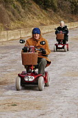 An elderly man is seen driving his motorized invalid scooter. - David Mansell - 25-12-2004