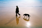 Beach walk feature for Travel. Freshwater Bay West in the Pembrokeshire national park, Wales. Man walking with his dog - David Mansell - 31-03-2001