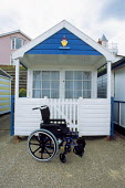 Disabled users wheelchair outside a hut, Suffolk Heritage Coast, Southwold. - David Mansell - 2000s,2002,accommodation,adult,adults,age,ageing population,bound,Coast,coastal,coasts,disabilities,disability,disable,disabled,disablement,elderly,england,Heritage,holiday,holiday maker,holiday maker