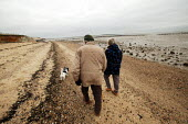 Retired old people seen walking with their dog along the beach at Cudmore Grove Country Park, East Mersea, Essex. - David Mansell - 12-12-2002