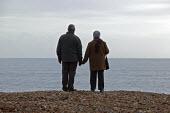 A married retired couple holding hands as they stand on a shingle beach on their winter walk along the seashore at Christchurch, Dorset - David Mansell - 28-12-2007