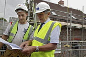 A site manager for the house building company Banner Homes talking with a subcontractor, while working on the construction of new homes in Chawton. - David Mansell - 10-07-2007