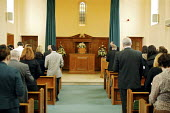 Mourners inside the chapel of rest during a funeral service at the local authority crematorium in Hillingdon. - David Mansell - &,2000s,2007,belief,burial,casket,ceremonial,ceremonies,ceremony,chapel,chapels,christian,christianity,christians,cities,city,coffin,coffins,conviction,cremated,cremation,crematorium,death,deaths,depr