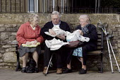 A retired elderly man and two women pensioners share their fish and chip lunch, while sitting down on a bench after their shopping visit to Bakewell on market day, in the Peak District National Park,... - David Mansell - 16-03-2009